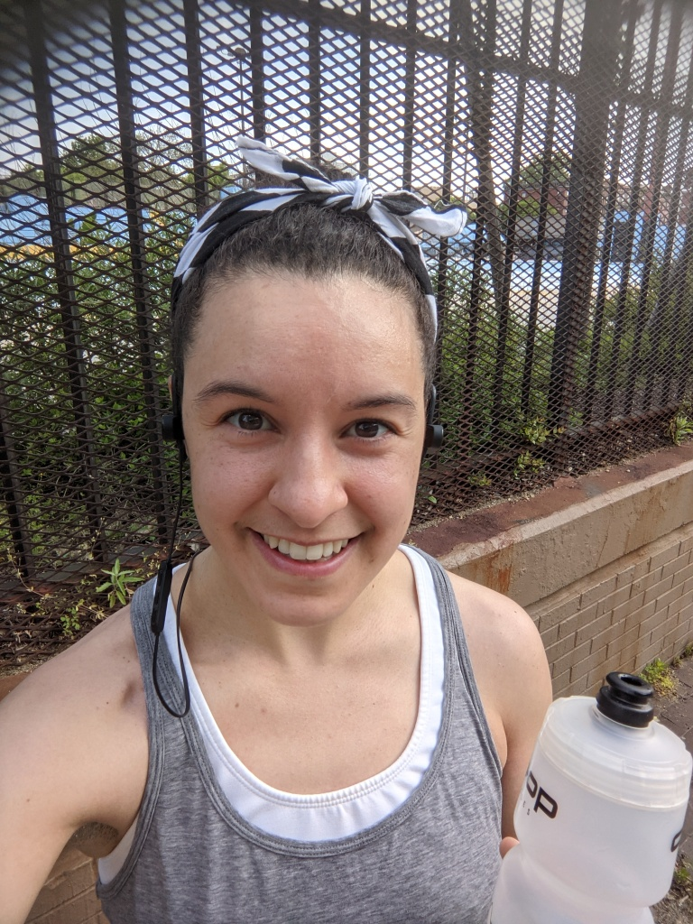 Shea - Smiling, but tired holding a water bottle and wearing workout gear.